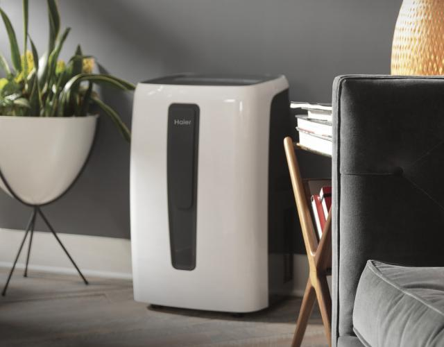 Photo of a Haier white portable air conditioner featured in a grey modern living room