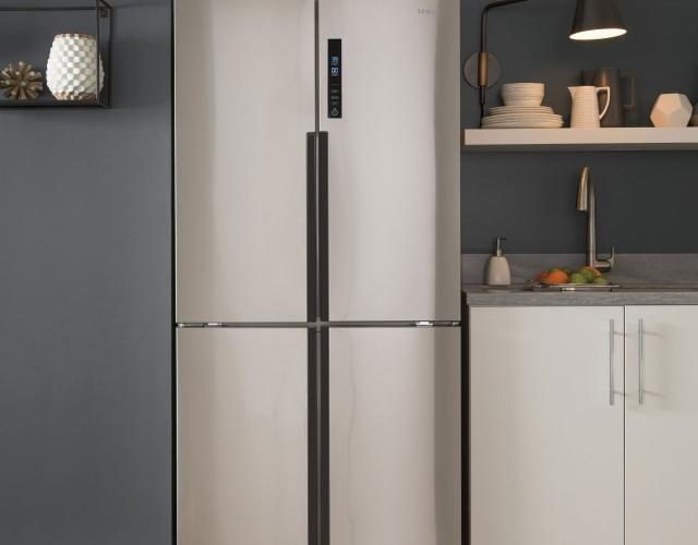 Photo of a Haier stainless steel quad door refrigerator featured in a contemporary kitchen