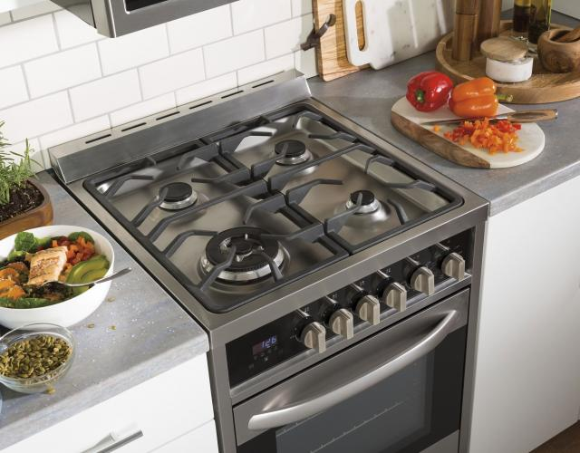 Photo of a Haier stainless gas range featured alongside a prepared grilled chicken salad