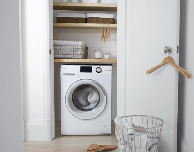 Photo of a Haier white washer dryer combo featured within a small hall closet